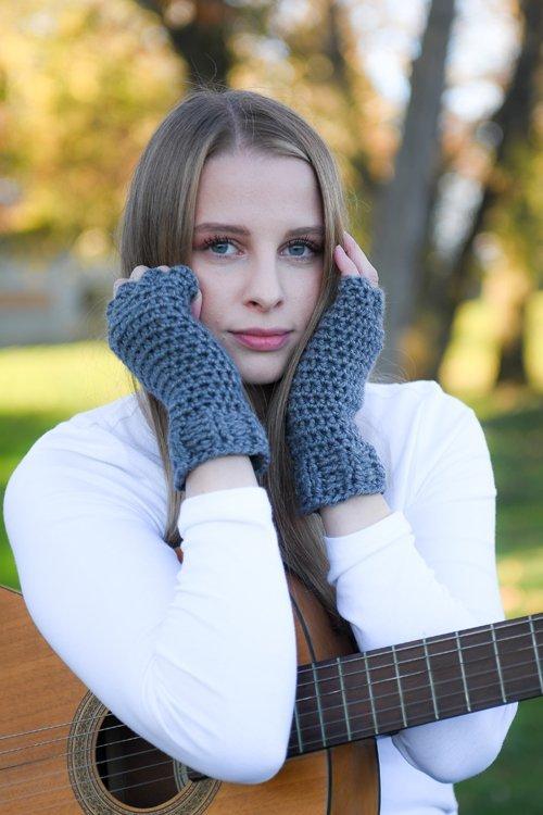 Denim Blue Finger Gloves - modeled - hands framing face leaning on a guitar