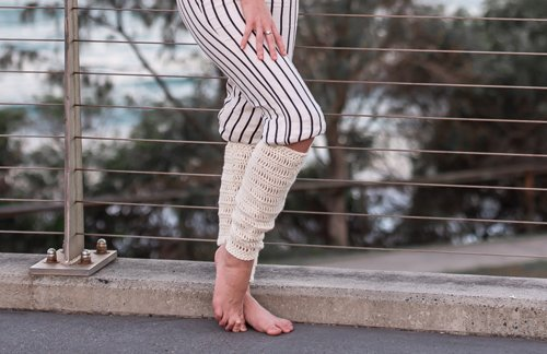 Cream Leg Warmers on woman standing - close up against a fence