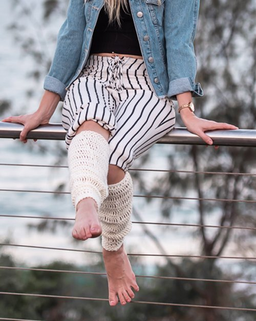 Bamboo Leg Warmers in cream - on woman standing - close up sitting on a fence