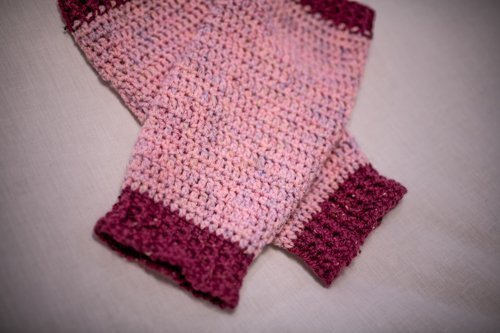 Pink and Cerese Valley Leg Warmers laid flat, crossed over each other - close up