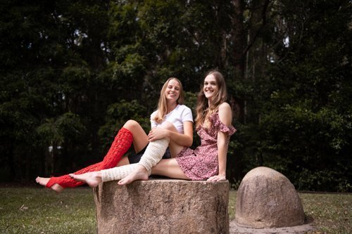 Red Laketown Socks on woman sitting next to another woman wearing Bamboo Leg Warmers