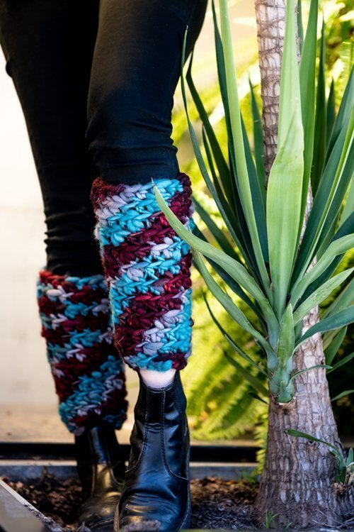 Super chunky multi-colored Leg warmers close-up on legs beside a plant - 2