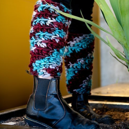 Super chunky multi-colored Leg warmers close-up on legs beside a plant - 3