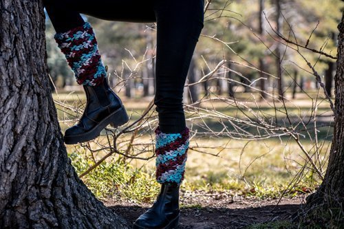 Super chunky multi-colored Leg warmers on a silohetted woman outside with trees
