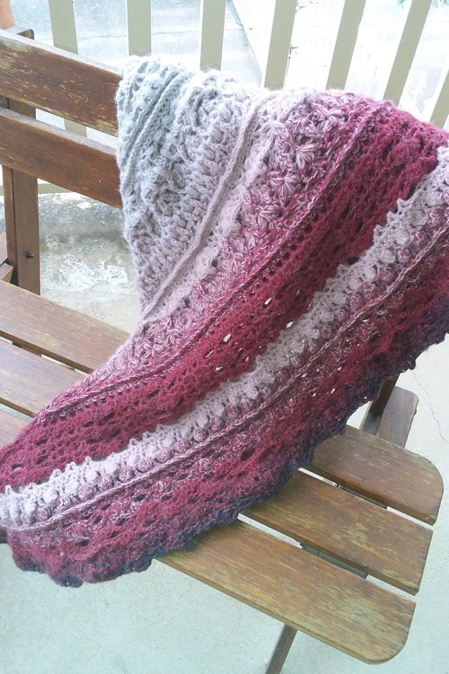 Journey Shawl - A thick triangle shawl in an ombre of cream, dusky pink, burgundy and a touch of charcoal - Draped on wooden chair - available from MadeforYOUbyFi April 2021