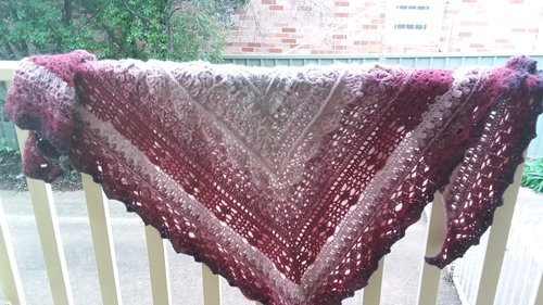 Journey Shawl - A thick triangle shawl in an ombre of cream, dusky pink, burgundy and a touch of charcoal - Wide shot on railing - available from MadeforYOUbyFi April 2021