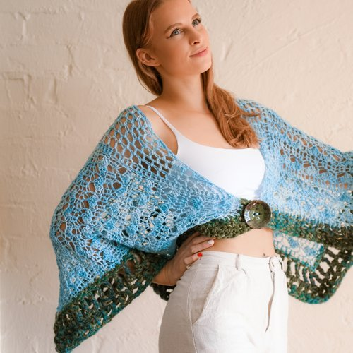 Strolling Along Shawl - in Ice Blue and Olive Green - on model with one arm outstretched - inside against cream brick wall - available from MadeforYOUbyFi April 2021