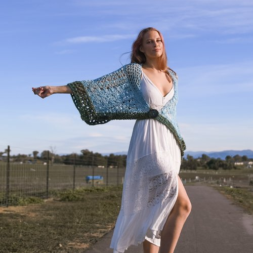 Strolling Along Shawl - in Ice Blue and Olive Green - on model with one arm outstretched - outside with big blue sky behind - available from MadeforYOUbyFi April 2021